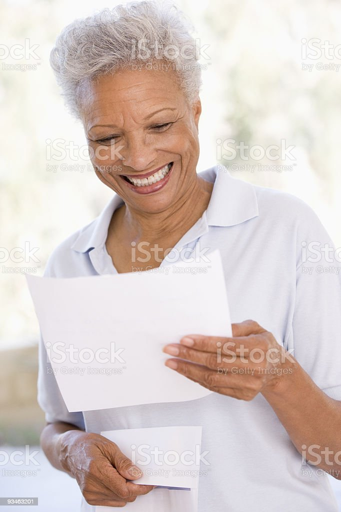 Woman reading letter smiling stock photo