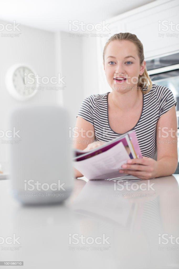 Mulher lendo revista em casa pergunta Digital assistente em casa - foto de acervo