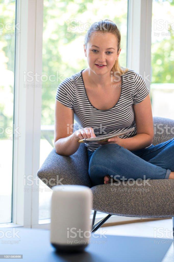 Mulher lendo revista em casa fazendo pergunta assistente Digital - foto de acervo
