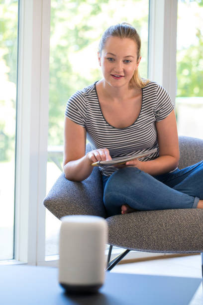 Woman Reading Magazine At Home Asking Digital Assistant Question stock photo