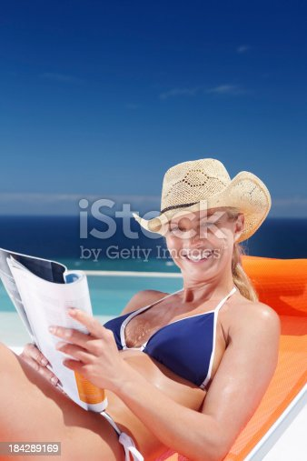 Portrait of smiling mature woman relaxing at beach while reading magazine