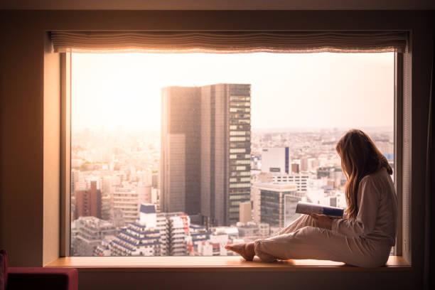 Woman reading magazine in hotel in Shibuya, Tokyo, Japan stock photo