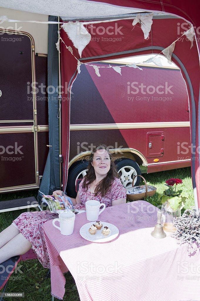 Woman reading magazine outside trailer stock photo