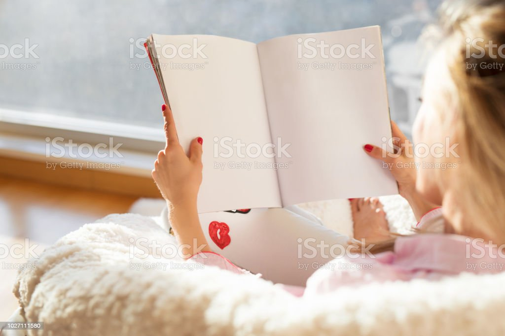 Woman reading magazine with empty white blank pages. Mockup and template for your own content. - foto stock