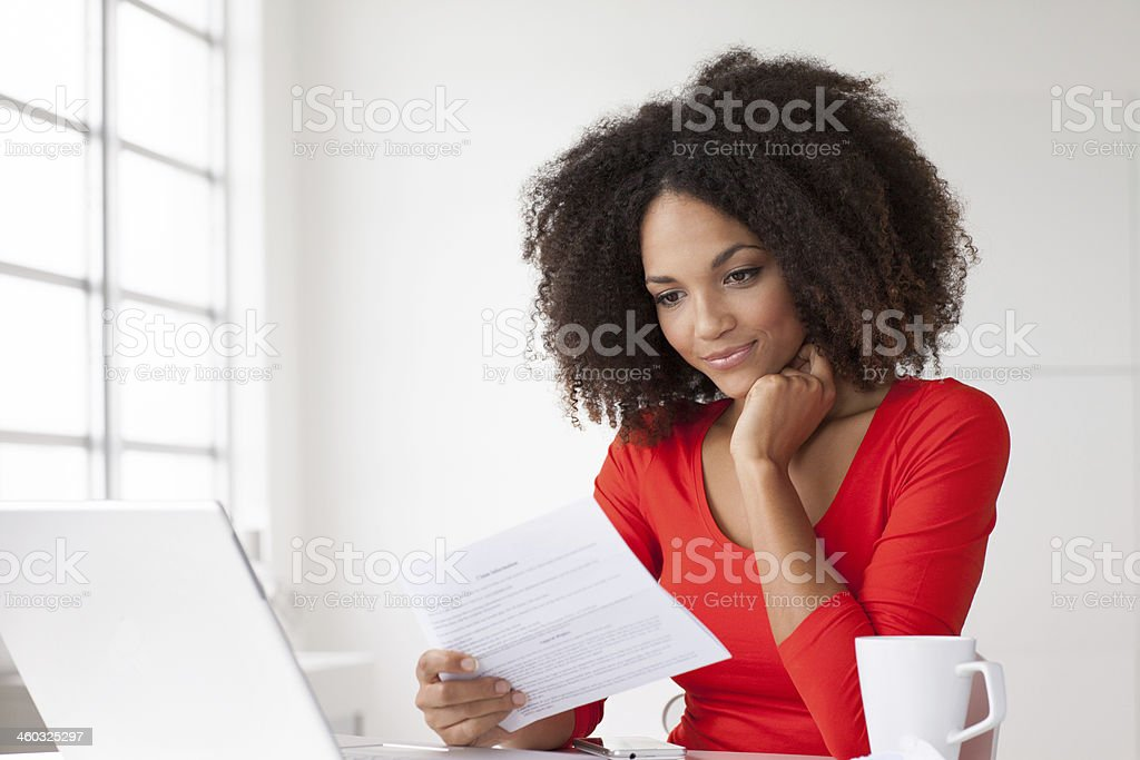 Woman reading mail at table stock photo