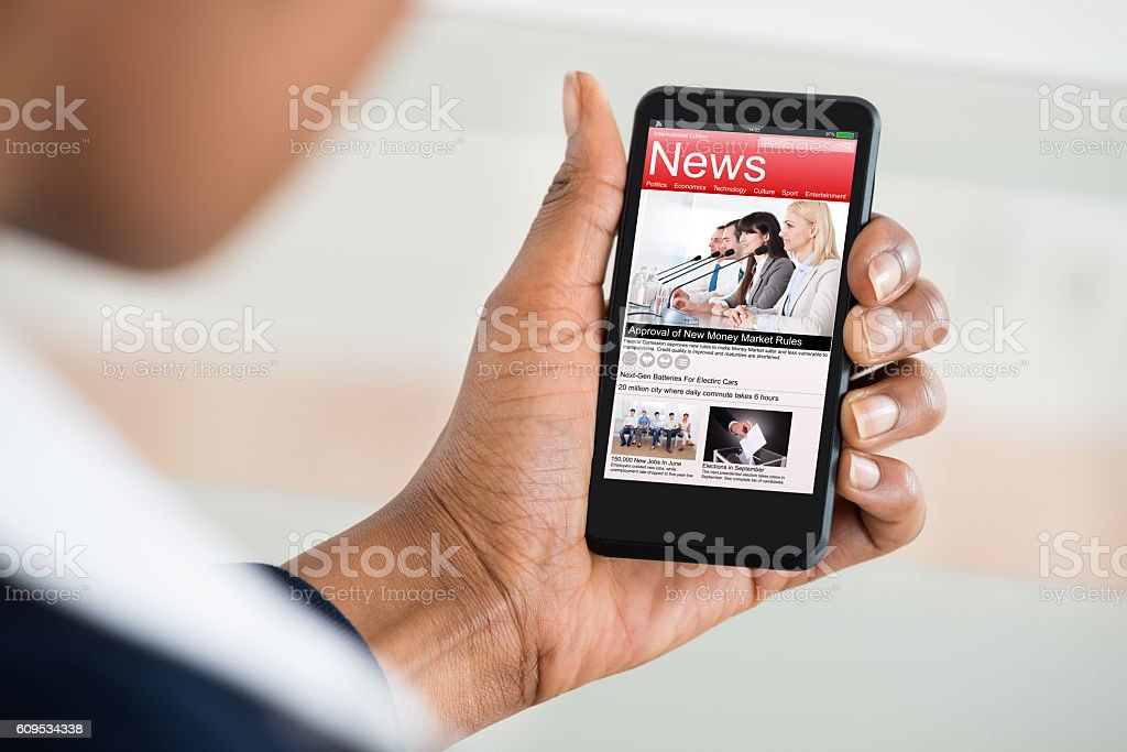 Woman Reading News On Mobile Phone stock photo