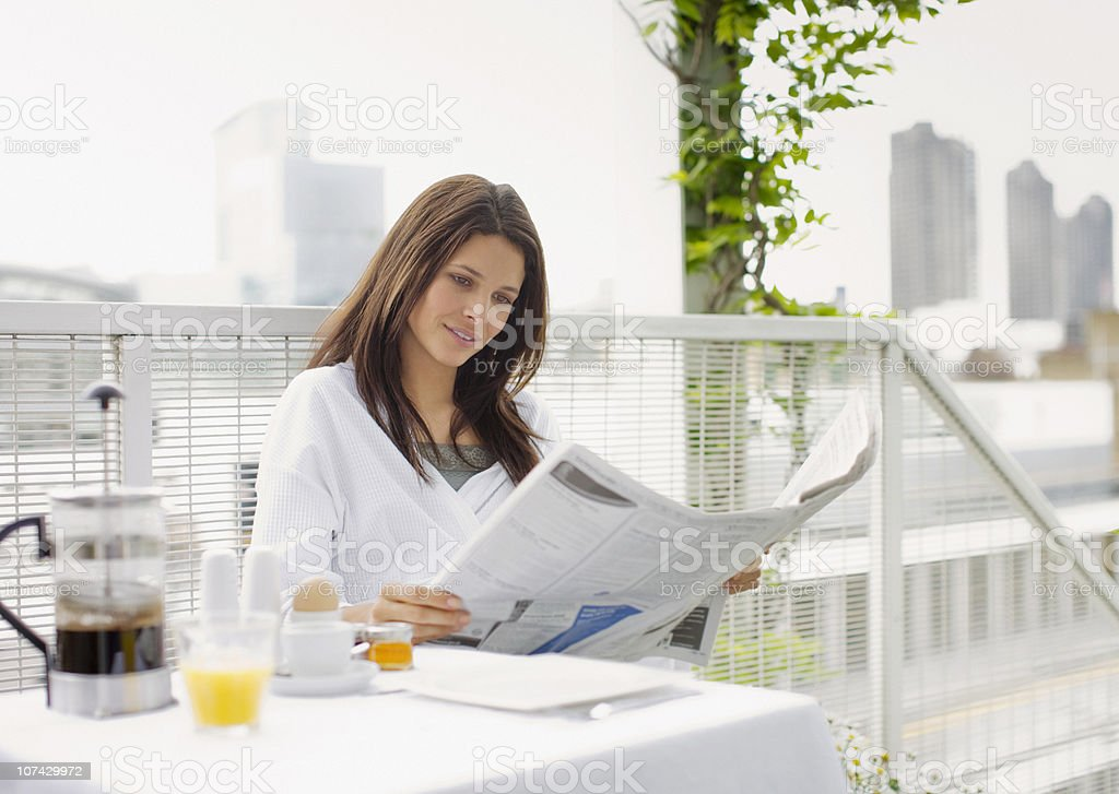 Woman reading newspaper and having breakfast on balcony stock photo