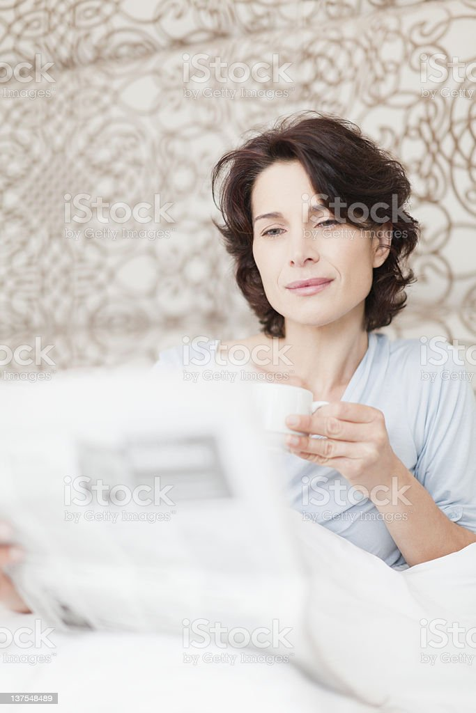Woman reading newspaper in bed royalty-free stock photo