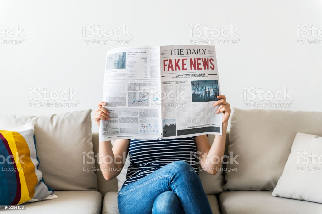 Woman reading newspaper on a couch stock photo