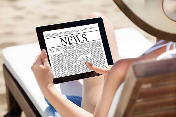 woman reading newspaper on digital tablet at beach - newspaper beach stockfoto's en -beelden