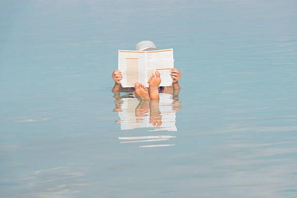 woman reading newspaper whilst floating in dead sea. - newspaper beach stockfoto's en -beelden