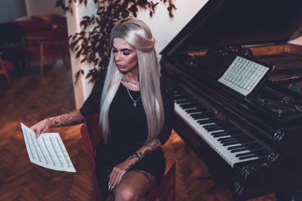 frau notenlesen und klavier spielen - musiknoten tattoos stock-fotos und bilder