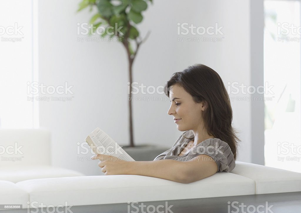 Woman reading on sofa royalty-free stock photo