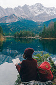 Young Caucasian woman reading notebook  on the background of  scenic view of Eibsee lake in  Bavarian Alps, Germany
