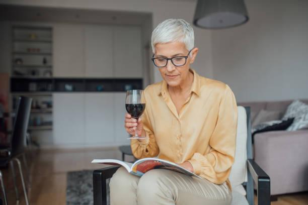 vrouw leest over een glas rode wijn - woman home magazine stockfoto's en -beelden