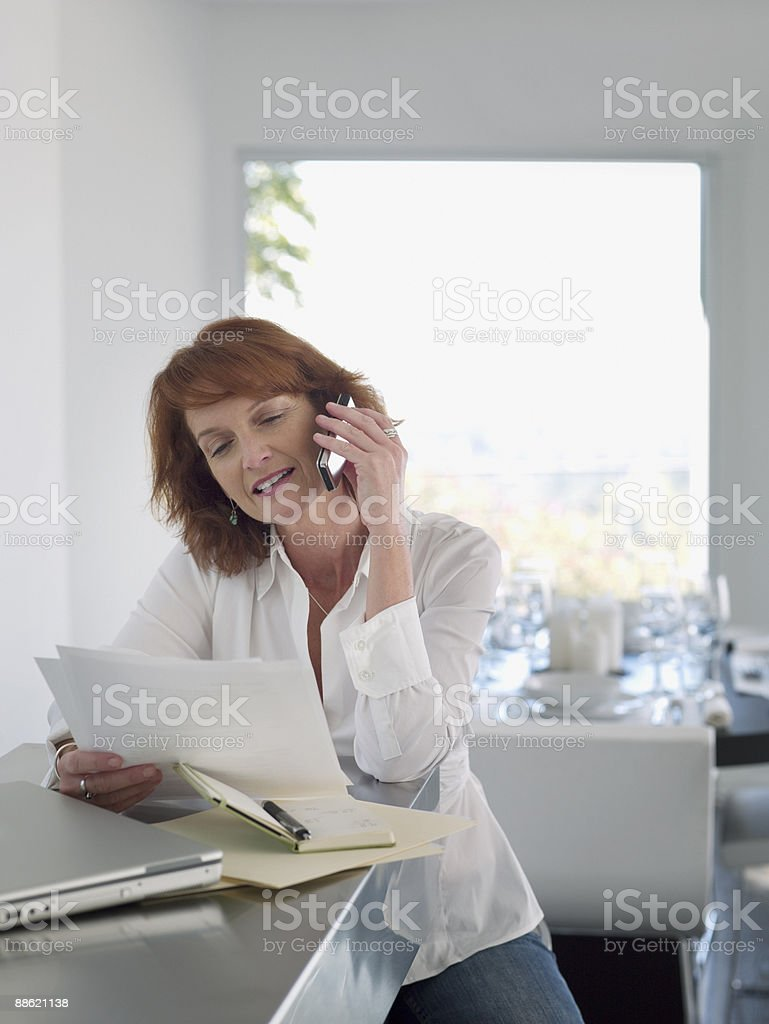 Femme, lecture de journaux et de parler sur téléphone portable photo libre de droits