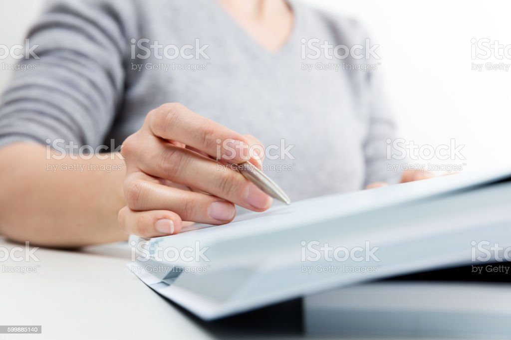 Woman reading, pen showing text in a book stock photo