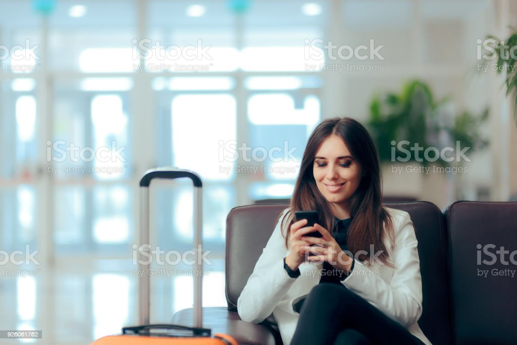 Woman Reading Phone Messages in Airport Waiting Room stock photo