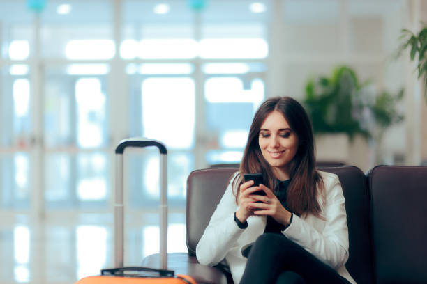woman reading phone messages in airport waiting room - airport check in counter stock pictures, royalty-free photos & images