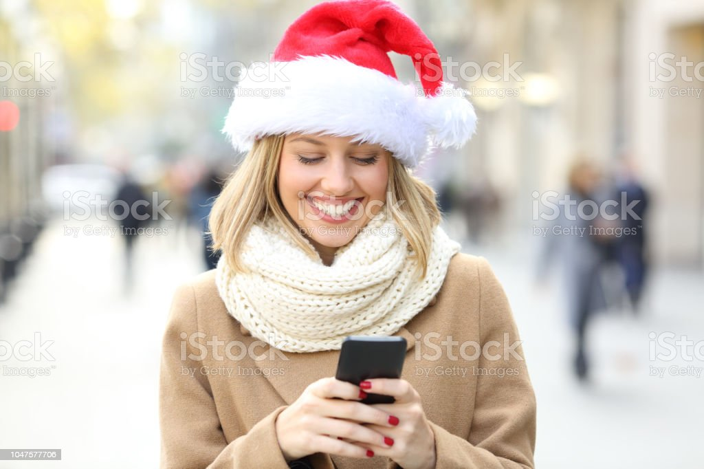 Happy woman wearing santa hat reading phone text on christmas in the...