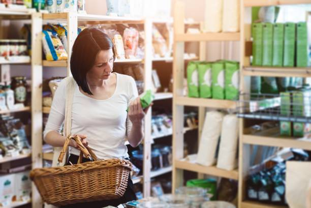 Woman reading product information on label Woman choosing products in ecological shop with healthy food and reading product information on label discount store stock pictures, royalty-free photos & images