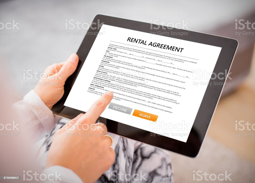 Woman Reading Rental Agreement On Tablet Stock Photo