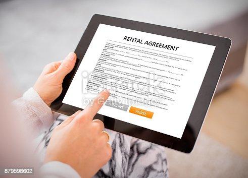 istock Woman reading rental agreement on tablet. 879598602