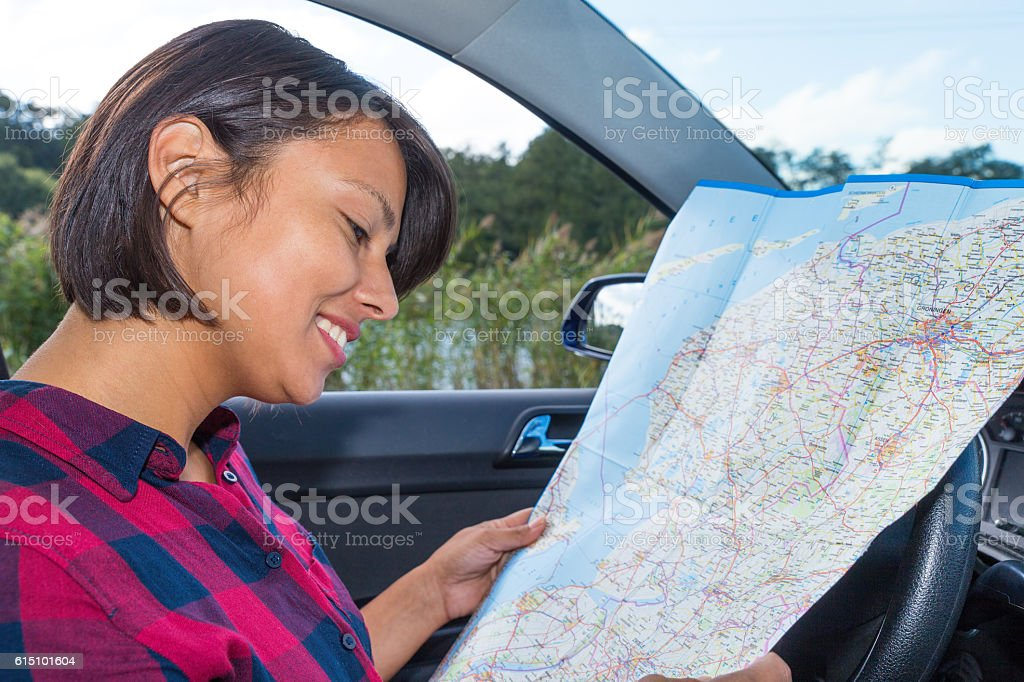 Woman reading road map in car outdoors stock photo