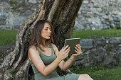 Woman reading tablet and enjoy rest in a park under tree. Castle of Bellinzona, Switzerland