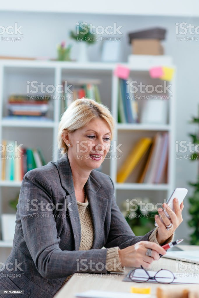 Woman reading text messages and writing down notes in office stock photo
