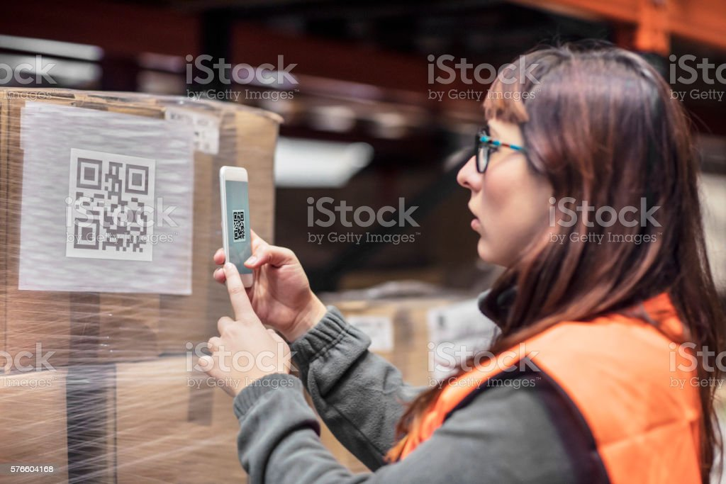 Woman reading the barcode with the mobile phone app​​​ foto
