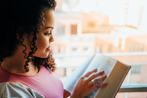 Woman reading the bible beside the window with natural light