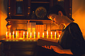 Beautiful young woman reading the book under the candlelight.