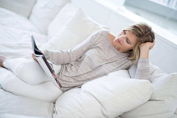 woman reading the newspaper at home - woman home magazine stockfoto's en -beelden