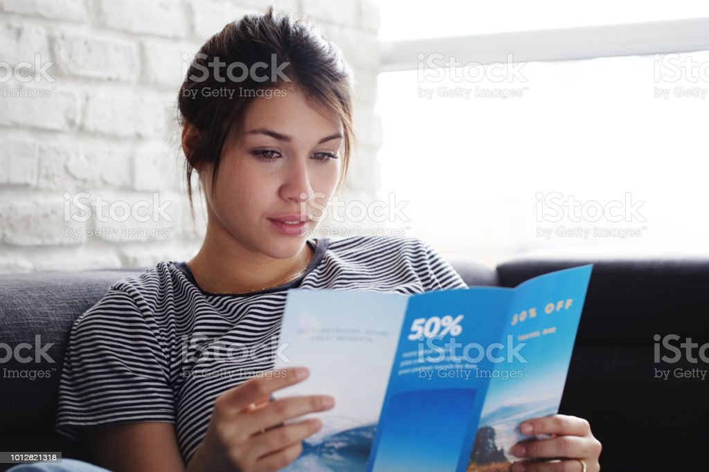 Woman Reading Travel Flye On Sofa At Home foto stock royalty-free