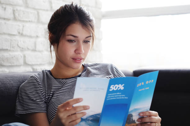 woman reading travel flye on sofa at home - flyer leaflet stock photos and pictures