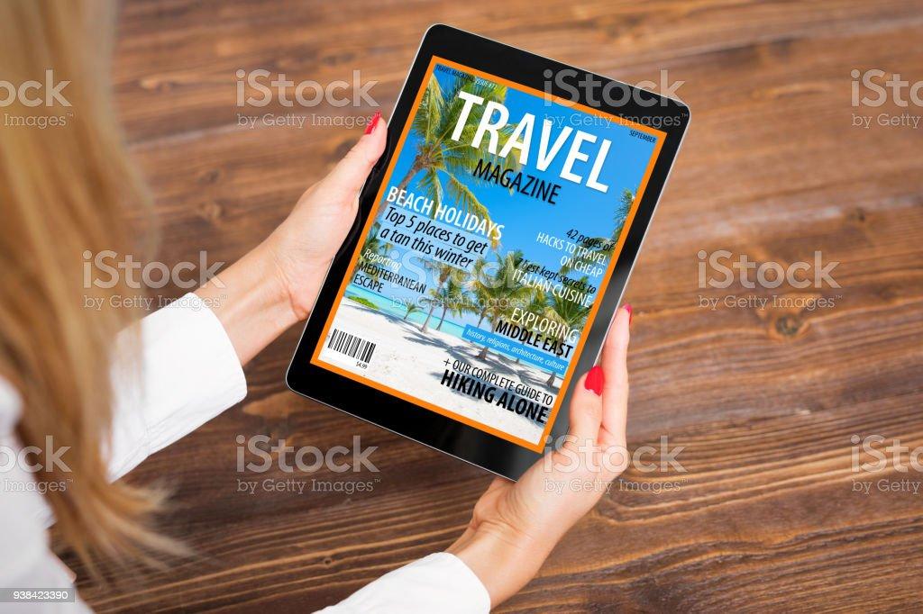 Woman reading travel magazine on tablet stock photo