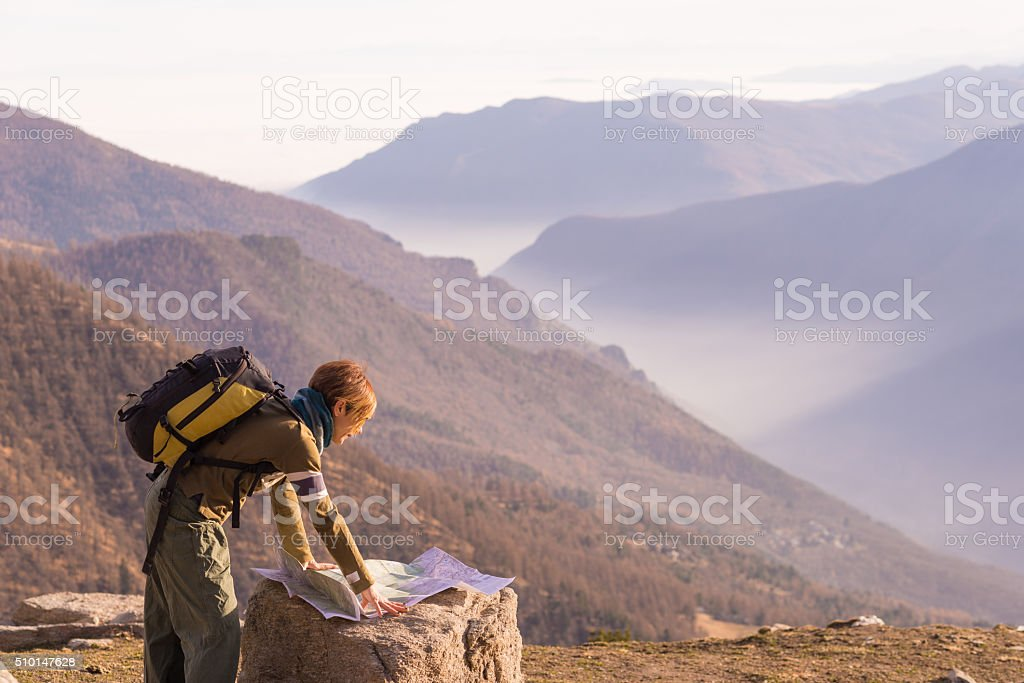 Woman reading trekking map at panoramic spot on the Alps stock photo