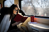 Woman reading while traveling with the train commuter journey sitting