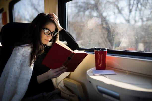 frau liest während der fahrt mit der bahn pendler reise sitzung - bahn reisen stock-fotos und bilder