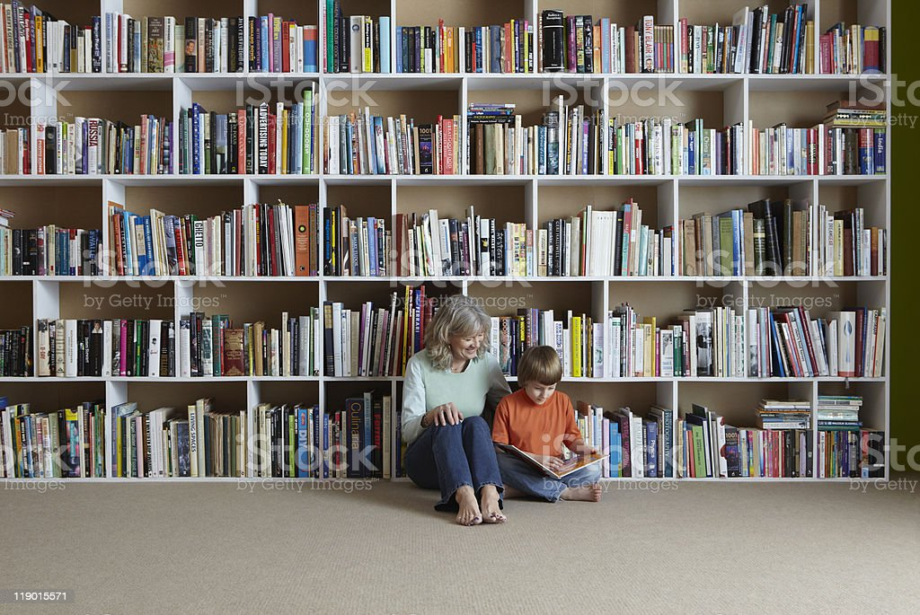 Woman reading with grandson by bookshelf stock photo
