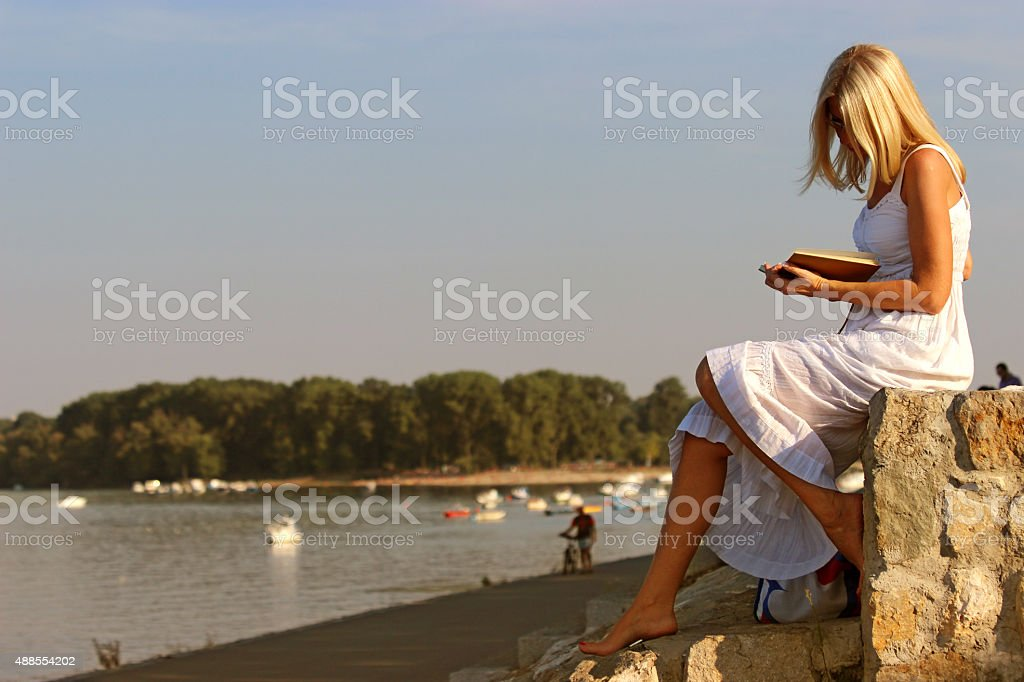 Woman reads a book on the river stock photo