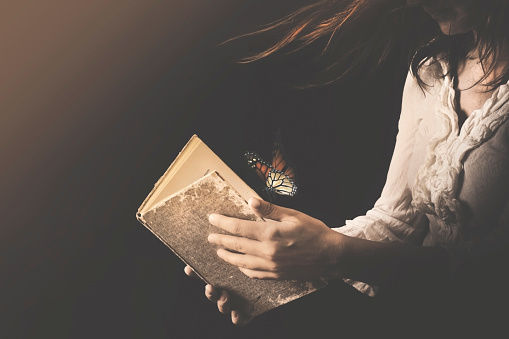 istock woman reads a book where butterflies go out 1072437676