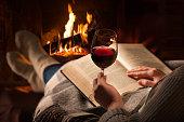Woman reads book near fireplace