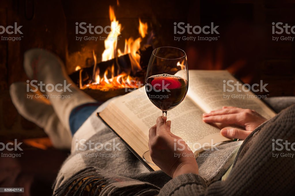 Woman reads book near fireplace stock photo