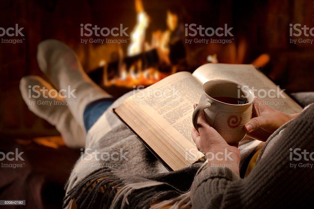 Woman reads book near fireplace stock photo