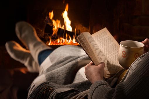 A képhez tartozó alt jellemző üres; woman-reads-book-near-fireplace-picture-id531466114 a fájlnév
