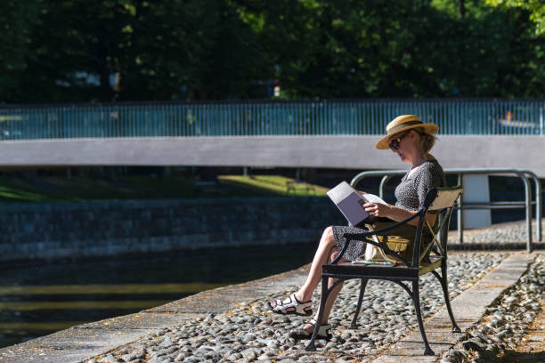 Woman reads newspaper on a park bech stock photo