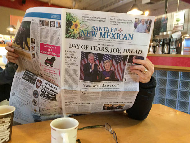 "woman reads newspaper with headline: ""day of tears, joy, dread"" - trump стоковые фото и изображения"