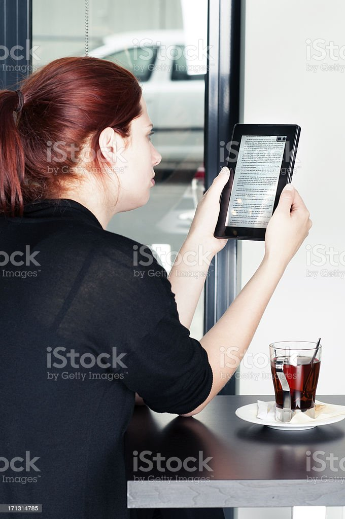 Woman reads on digital tablet or ereader at a cafe royalty-free stock photo